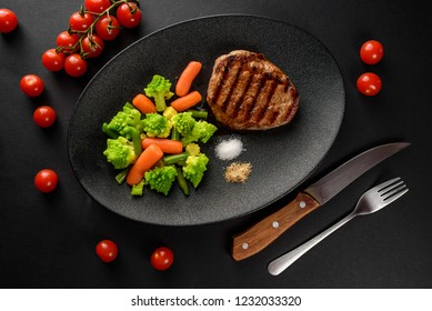 steak with vegetables served on a black plate