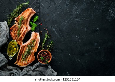 Steaks on the bone with rosemary. Grill, barbecue. On a black stone background. Top view. Free copy space.