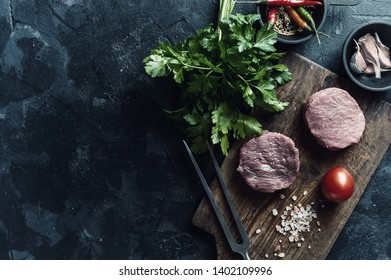 Steaks on cutting board, ready to cooking. Fresh raw meat, wooden background, flat lay. Vintage stylization, retro film filter