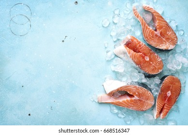 Steaks of raw salmon on ice on a blue slate,stone or metal background.Top view with space for text.
