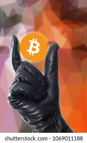 Stealing bitcoin concept with black leather glove holding the coin