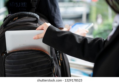 Stealing form backpack,Woman thief steal a laptop from backpacker,Beware of pickpockets,Man focusing at smartphone without knowing someone try to steal laptop from his rucksack,Woman thief steal.