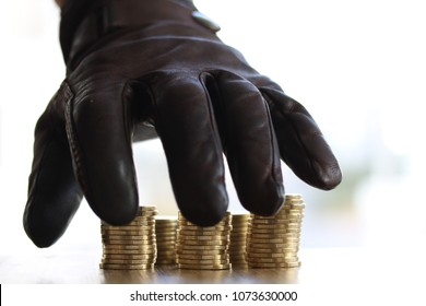 Stealing money - Greedy hand with black gloves grabbing or reaching out for pile of golden coins. Close up - Concept for tax, fraud and greed