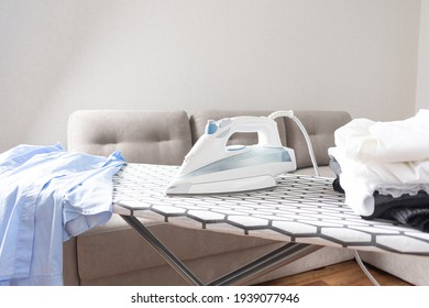 Steam blue iron on ironing board. Clothes, ironing board household concept