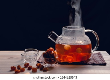 The steam from a cup or pot of tea on the old wood table and black background with nature light by window in the morning, Warm drinks make good healthy, Longan juice has many benefits,Selective focus.