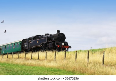 A steam engine pulling a passenger carriage on the track along the Swanage railway network. Location in Dorset UK.