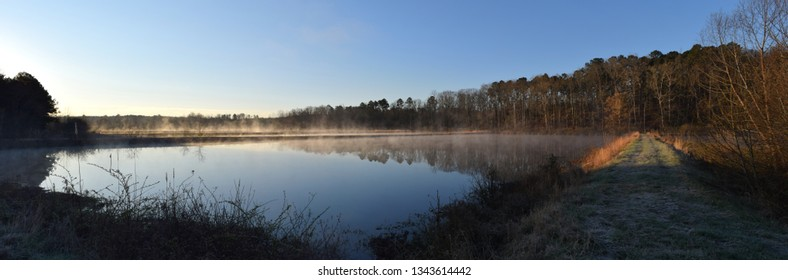 Steam fog rises from a pond in Mississippi on a spring morning