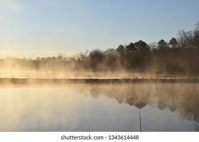 Steam fog rises from ponds at sunrise in Mississippi