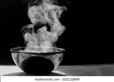 Steam of hot soup with smoke  in a soup  black ceramic bowl on dark background.selective focus. black and white tone