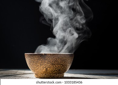 Steam of hot soup with smoke  in a soup  black ceramic bowl on dark background.selective focus