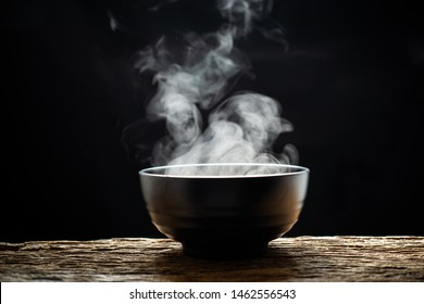 Steam of hot soup with smoke wood bowl on dark background.selective focus.hot food concept