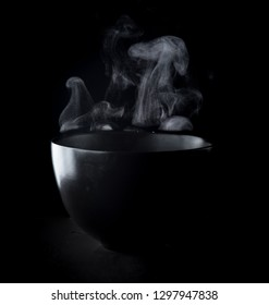 Steam of hot water in a bowl with smoke over dark background
