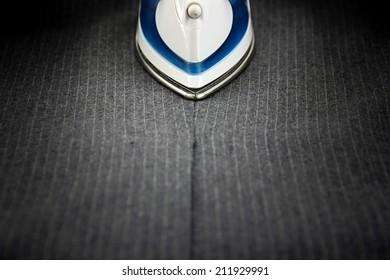 Steam iron on men's suit.