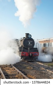 Steam locomotive approaching in train yard with lots of steam released
