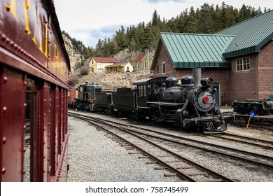 Steam locomotive of Georgetown loop railroad in Colorado, USA. Engine is parked in a depot, looking from another coach.