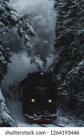 Steam locomotive of the Harzer Brockenbahn traveling through a snow-covered winter forest
