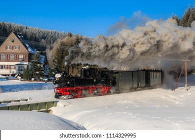 Steam locomotive in the winter landscape. Ore Mountains, Saxony, Germany