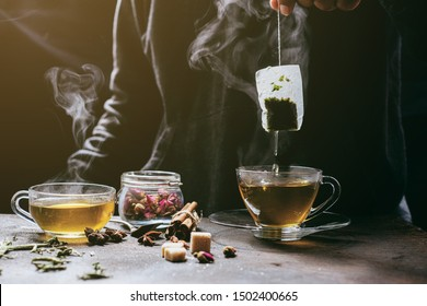 The steam from man with jecket Jean is soaking tea bag on vintage white cup, preparing hot tea.Dipping teabag on cup,hot food and healthy meal concept