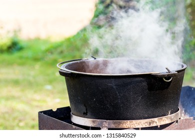 Steam over iron cauldron, meal is preparing in an iron pot outdoors. Camping in the nature and preparing food concept