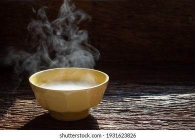 The steam from Rice milk and rice on wood back ground.A Bowl of Asian Rice Porridge or Soft Boiled Rice