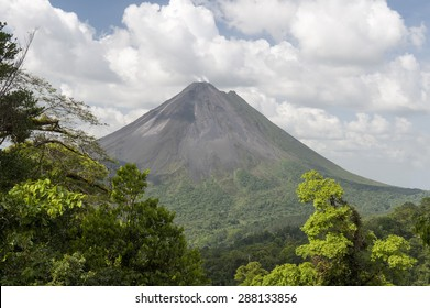 Steam rises from Arenal volcano in Cost Rica is framed by the beautiful tropical rain forest of La Fortuna.  Arenal is one of seven major volcanos in the country.