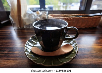 Steam rises from hot black coffee on beautiful wooden cafe table next to window