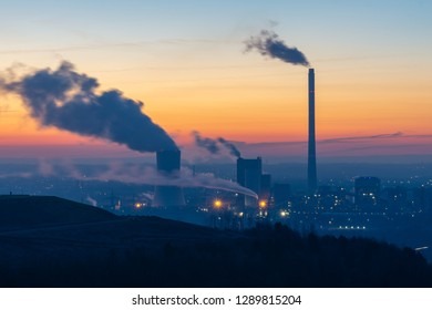 Steam rises from a smokestack on a factory silhouetted against the sunlight at sunrise