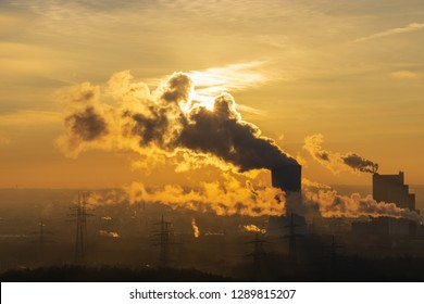 Steam rises from a smokestack on a factory silhouetted against the sunlight golden hour