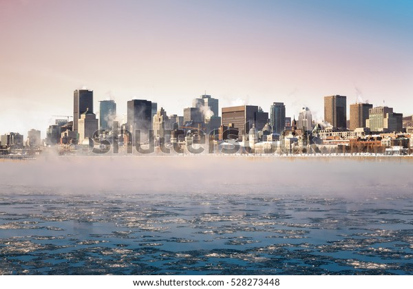Steam rising from the frozen St Lawrence river at sunrise, with the Downtown district of Old montreal in the background.