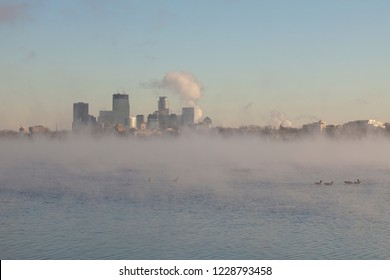 Steam rising from Lake Bde Maka Ska with Minneapolis skyline.
