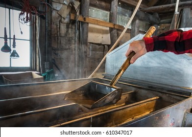 steam rising off of boiler evaporating  maple tree sap to make maple syrup in sugar house, worker ladling syrup to test  how thick syrup has become ; an early spring tradition in Vermont