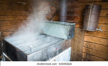 steam rising off of boiler evaporating  maple tree sap to make maple syrup in sugar house, an early spring tradition in Vermont