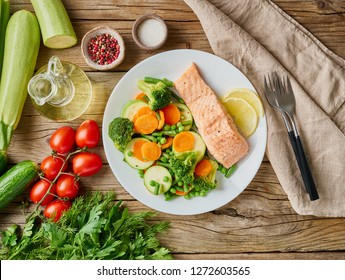 Steam salmon and vegetables, Paleo, keto, fodmap diet. White plate on old rustic wooden table, top view