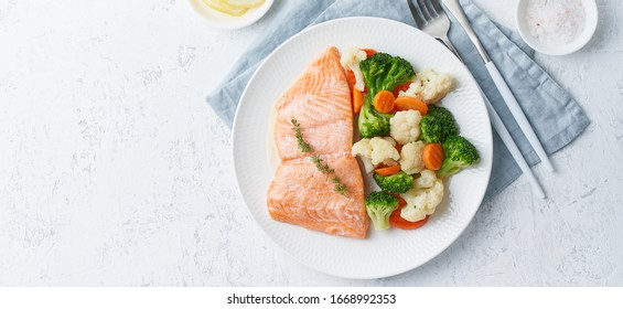 Steam salmon and vegetables, Paleo, keto, fodmap, dash diet. Mediterranean diet with steamed fish. Healthy concept, white plate on gray table, gluten free, lectine free, top view, long banner