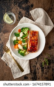 Steam salmon and vegetables, Paleo, keto, fodmap, dash diet. Mediterranean food with steamed fish. Oven baked asian dish with teriyaki. Healthy concept, gluten free, lectine free, top view, vertical