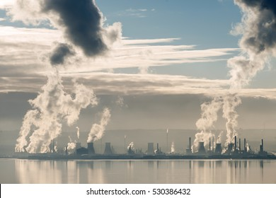 Steam and smoke emissions from the petrochemical plant at Grangemouth in Scotland on a still day in winter.