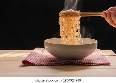 Steam and smoke Instant noodles in bowl on wooden table and nature light and black background, selective focus. It is a convenient and inexpensive food, but eating often is not good for health.