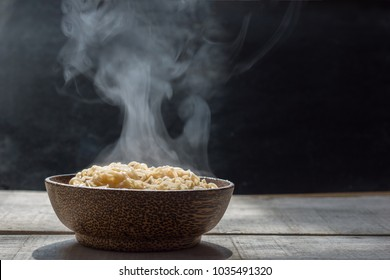 steam and smoke noodles in bowl on wooden background, selective focus