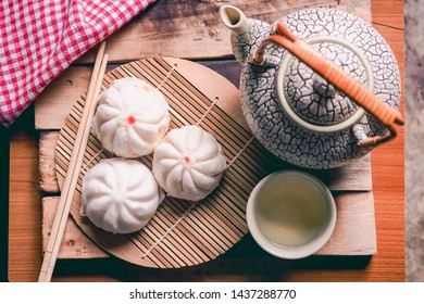 Steam stuff Buns (Sa La Pao) stuffed chinese snack with Chinese pot tea in dim light on wooden background still life .