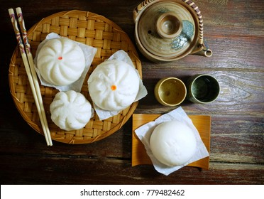 Steam stuff Buns (Sa La Pao) Stuffed  Chinese snack with Japanese tea pot in dim light on wooden background  still life image.