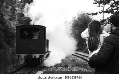 Steam train arrival. Attraction for kids and parents. Azpeitia, Spain. Father holding daughter closing ears because of noisy locomotive whistle. Selective focus. Black and white photo.
