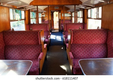 Steam train carriage seats, luxurious red seats with tables, on a sunny day in the UK.