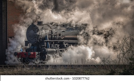 A steam train locomotive emerges from the mist, steam and smoke taken in a landscape side on view