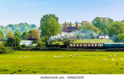 A steam train on the Kent and East Sussex Railway pulls away from to Bodiam Station, Sussex in springtime