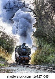 Steam train puffing along the tracks