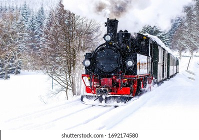 Steam train rushes through the snow-covered forest. Winter steam train view. Steam train ride in winter snow forest