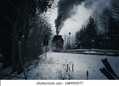The steam train winds its way through the snow to twilight
