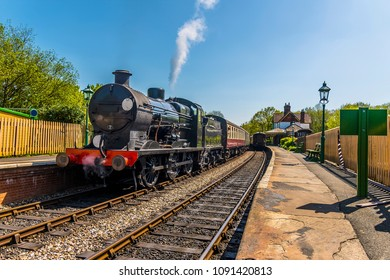 Steam trains at a station on a railway line in Sussex, UK on a sunny summer day