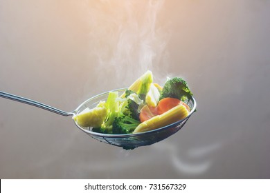 The steam from the vegetable colander in the dark,hot food and healthy meal concept
