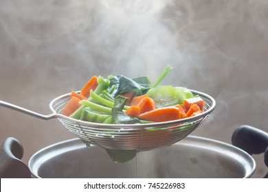 The steam from the vegetable colander in the darkSelective focus.
